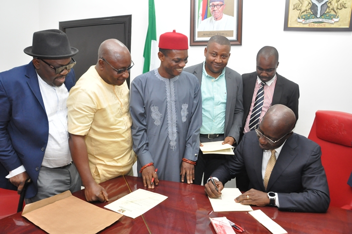 Edo State Governor, Mr. Godwin Obaseki, signing the 2018 appropriation bill into law, before the Speaker, Edo State House of Assembly, Rt. Hon. Kabiru Adjoto (middle), at the Government House in Benin City, Edo State capital, on Friday, December 29, 2017.
