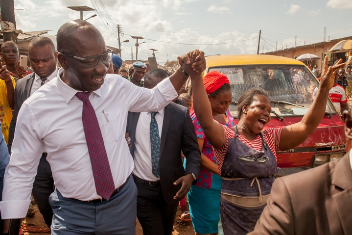 Edo State Governor, Mr. Godwin Obaseki (left), acknowledging cheers from traders, during his tour of Ekiosa Market, in Oredo Local Government Area, Edo State.