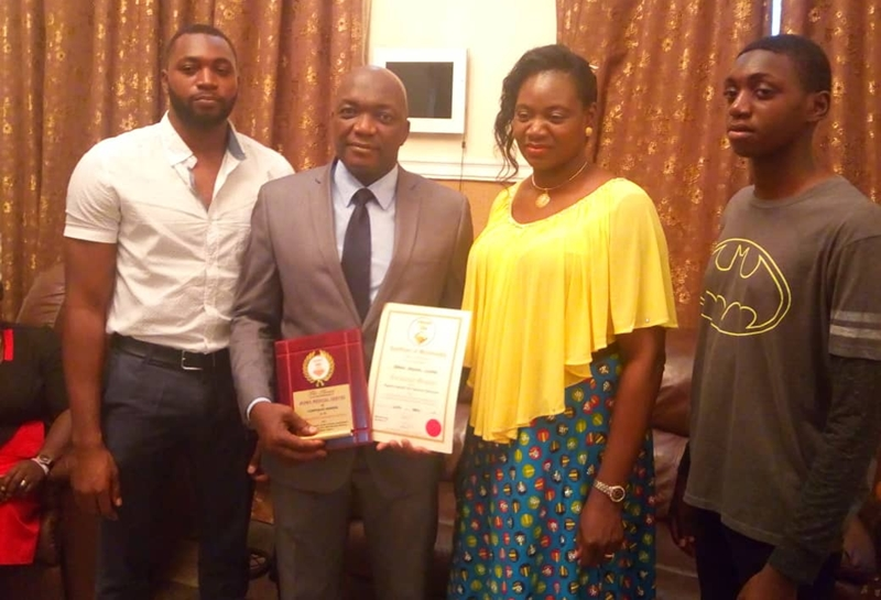 Dr. Osamwonyi Irowa displaying the award flanked by his wife and others