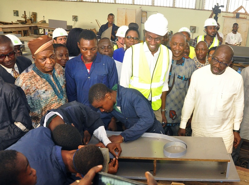 Edo State Governor, Mr. Godwin Obaseki (right), inspecting furniture produced by students of the vocational arm of Government Science and Technical College, during his inspection of the ongoing rehabilitation work at the College in Benin City, Edo State, on Friday.