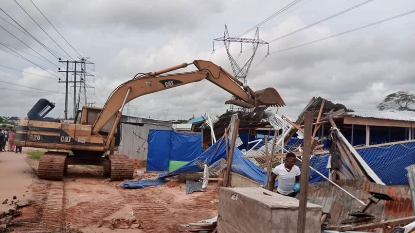 A bulldozer from the Ministry of Physical Planning and Urban Development, removing illegal structures at Abuja Quarters in Ugbor area of Benin City.